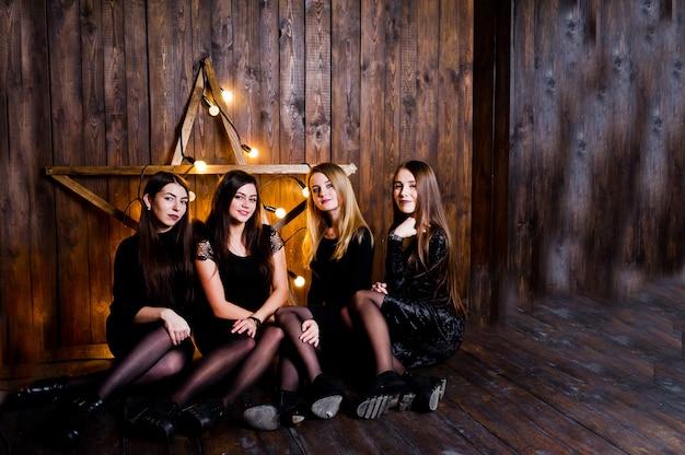 Cztery urocze przyjaciółki noszą czarne sukienki na tle dużej jasnej ozdoby świątecznej na drewnianej ścianie