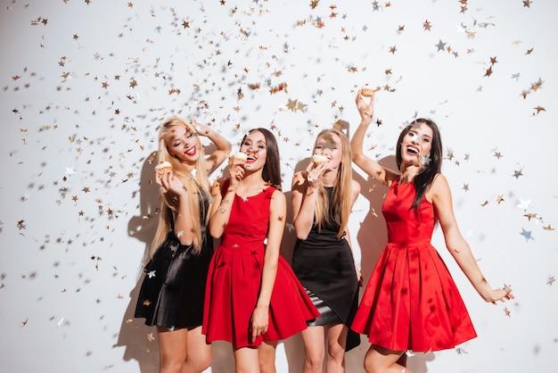 Cztery wesołe piękne młode kobiety tańczą i jedzą babeczki na imprezie na białym tle