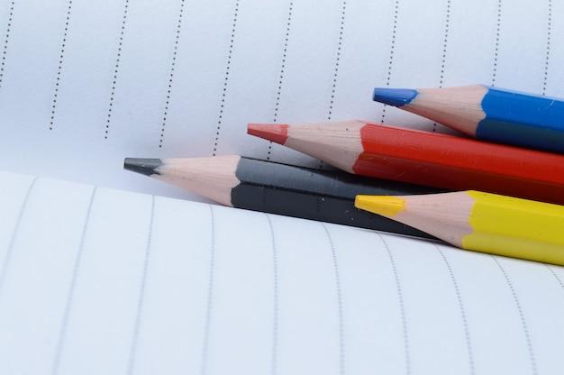 Cztery wielokolorowe ołówki - niebieska, czerwona, żółta, czarna. leżeć na otwartym notatniku.
