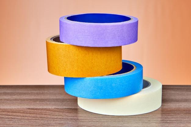 Cztery wielokolorowe taśmy klejące lub taśmy klejące są ułożone jedna nad drugą na stole, na pomarańczowo.