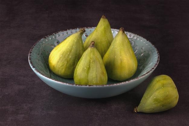 Cztery zielone figi na niebieskim talerzu i jedna figa obok granitowego stołu