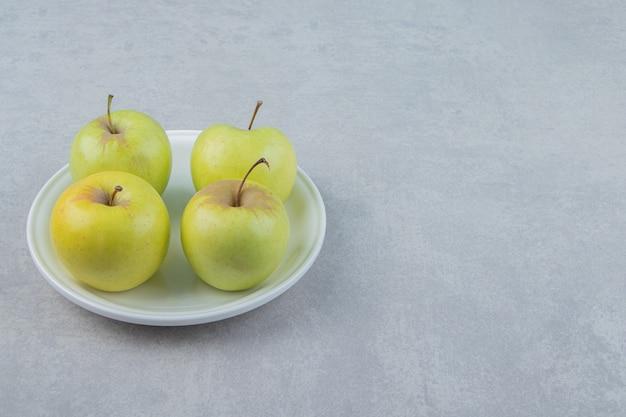 Cztery zielone jabłka na białym talerzu