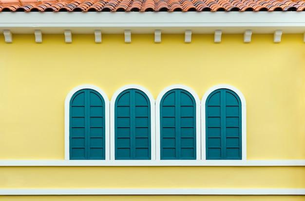 Cztery zielone łukowe okna na żółtej ścianie domu we włoszech w stylu retro