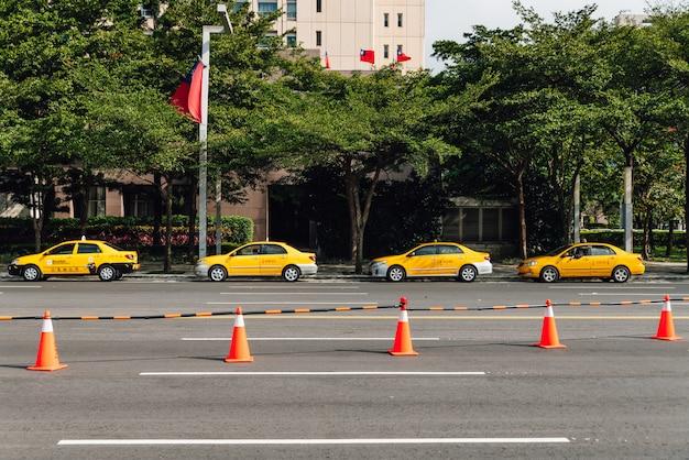 Cztery żółte taksówki czekają na klientów wzdłuż ulicy w pobliżu parku z pomarańczowymi szyszkami.
