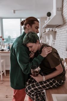 Czuć się beznadziejnie. dziewczyna czuje się beznadziejna po poważnych problemach rodzinnych, opierając się na ramieniu swojego wspierającego mężczyzny