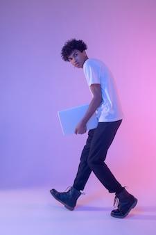 Czuć się dobrze. ciemnoskóry młody chłopak w białej koszulce z laptopem