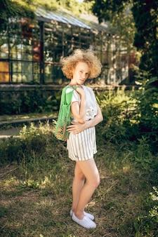 Czuć się dobrze. młoda kobieta z kręconymi włosami czuje się dobrze w słoneczny dzień