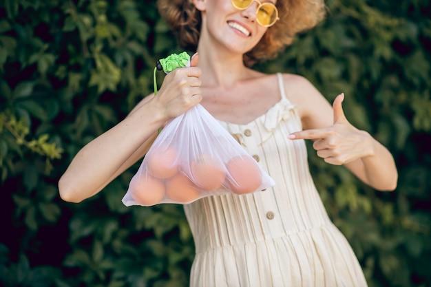 Czuć się dobrze. młoda uśmiechnięta kobieta z nektaryną w dłoni czuje się niesamowicie