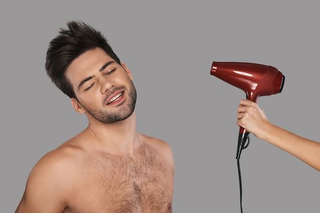 Czuć się dobrze. przystojny młody mężczyzna suszy włosy i uśmiecha się stojąc na szarym tle