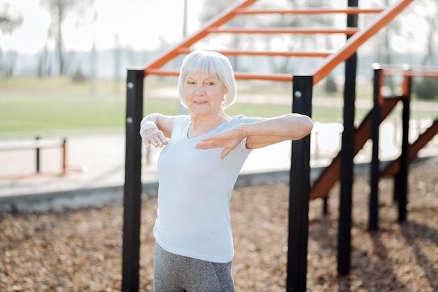 Czuć się dobrze. zainspirowana blond kobieta uśmiecha się i ćwiczy na świeżym powietrzu
