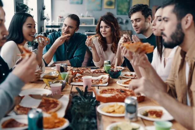 Czuć się głodnym. grupa młodych ludzi w strojach codziennych jedzących pizzę i uśmiechających się podczas kolacji w pomieszczeniu