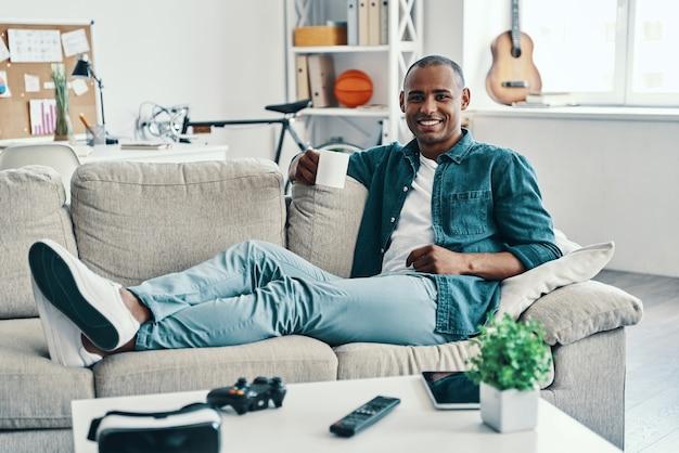 Czuć się komfortowo. przystojny młody afrykański mężczyzna patrzący na kamerę i uśmiechający się siedząc w pomieszczeniu