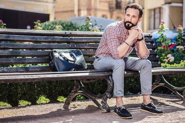 Czuć się nieszczęśliwym. zdenerwowany dorosły mężczyzna siedzący na ławce doświadczający awarii