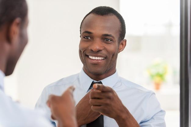 Czuć się pewnym siebie. młody afrykanin poprawia swój krawat i wskazuje się na lustro