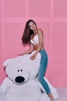 Czuć się pięknym. atrakcyjna młoda kobieta bawi się dużym misiem-zabawką i uśmiecha się stojąc na różowym tle