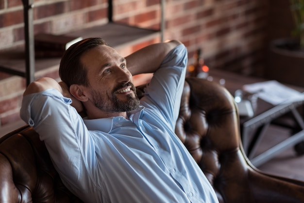 Czuć się świetnie. pozytywny szczęśliwy brodaty biznesmen siedzi na kanapie i kładąc ręce za głowę, ciesząc się relaksem