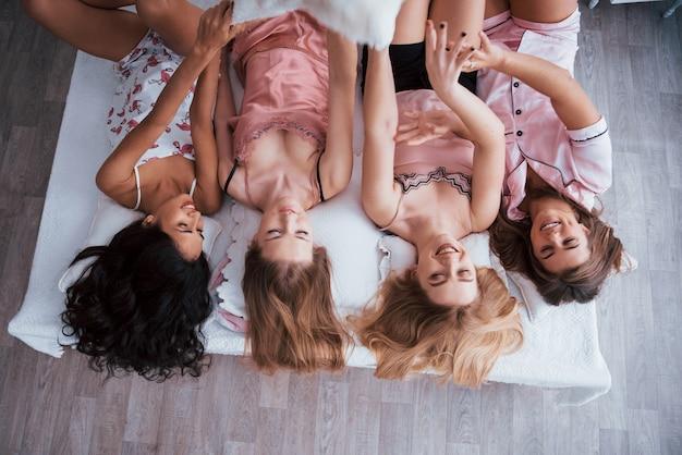 Czuć się usatysfakcjonowanym. odwrócony portret uroczych dziewczyn leżących na łóżku w nocnej bielizny. widok z góry