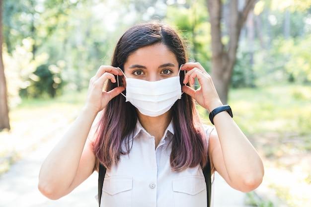 Czuć się wolnym. młoda kobieta sama w parku zdejmuje maskę medyczną i oddycha radośnie
