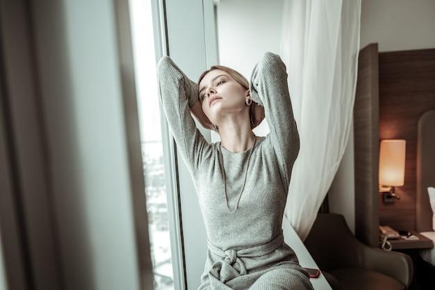 Czuć się wykończonym. młoda kobieta, patrząc przez okno, czując się wyczerpana po ciężkim dniu w biurze