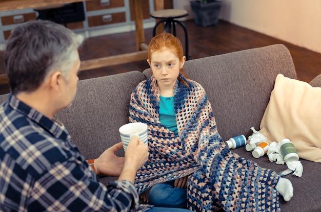 Czuć się zmęczonym. poważna ponura dziewczyna patrząca na swojego ojca siedząc na kanapie