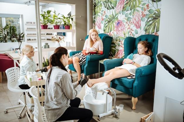 Czuć się zrelaksowany. modna piękna matka i córka czują się zrelaksowani spędzając dzień w salonie piękności