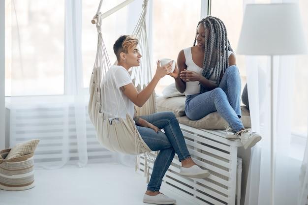Czuć się zrelaksowanym. dwie dziewczyny piją kawę w jasnym pokoju i wyglądają na zrelaksowane