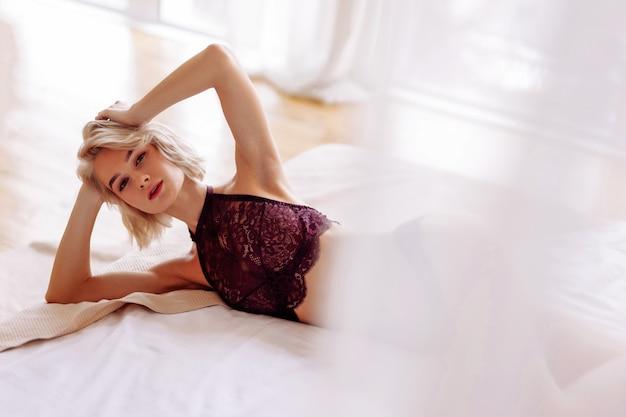 Czuć się zrelaksowanym. szczupła młoda blond kobieta z krótkimi włosami czuje się zrelaksowana podczas leżenia w łóżku