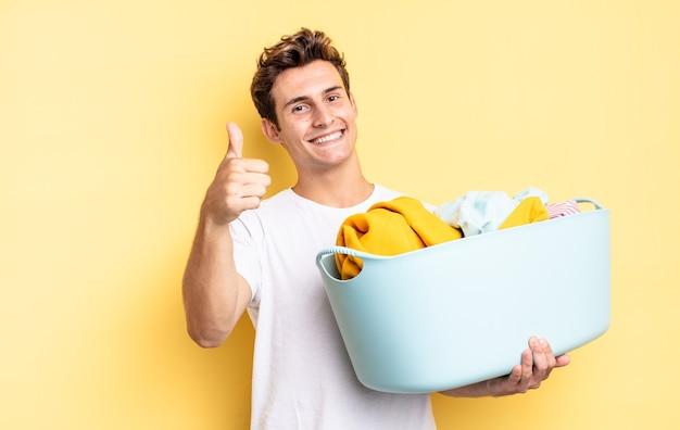 Czując się dumny, beztroski, pewny siebie i szczęśliwy, uśmiechając się pozytywnie z kciukami do góry. koncepcja prania ubrań
