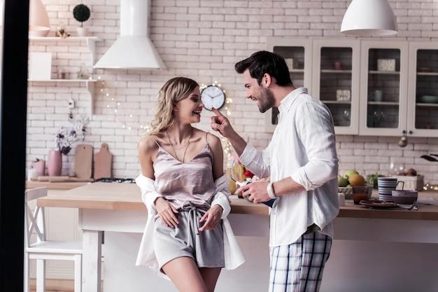 Czując się dziecinnie. brodaty ciemnowłosy młody mężczyzna w białej koszuli i jego piękna żona świetnie się czują podczas spędzania razem miłego weekendu