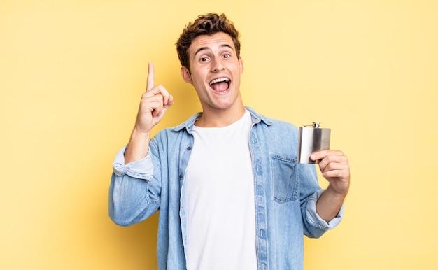 Czując się jak szczęśliwy i podekscytowany geniusz po zrealizowaniu pomysłu, radośnie podnosząc palec, eureka!. koncepcja kolby z alkoholem