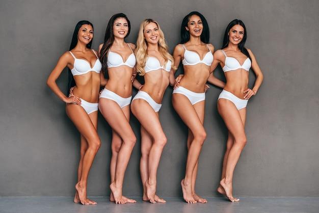 Czując się komfortowo w swojej skórze. pełna długość pięciu pięknych kobiet w bieliźnie obejmujących i uśmiechających się, stojąc na szarym tle