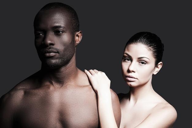 Czując się pewnie blisko niego. portret bez koszuli afrykańskiego mężczyzny i kaukaskiej kobiety, którzy łączą się ze sobą, stojąc na szarym tle
