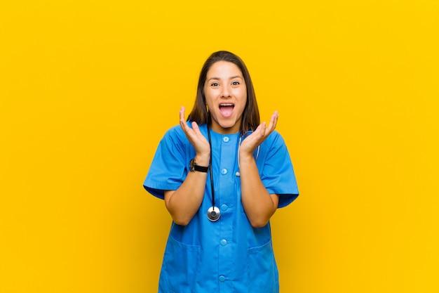 Czując się zszokowanym i podekscytowanym, śmiejąc się, zdumiony i szczęśliwy z powodu niespodziewanej niespodzianki na tle żółtej ściany