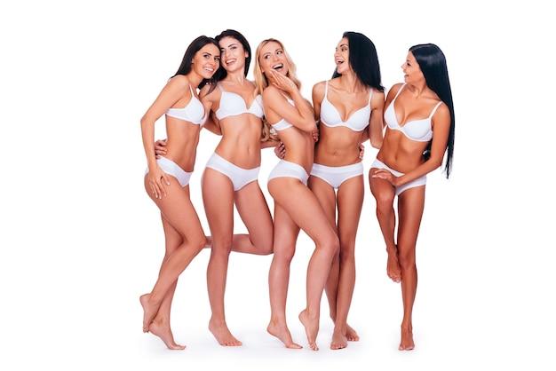 Czuję się dobrze i świetnie wyglądasz. pełna długość pięciu pięknych kobiet w bieliźnie pozujących i wyglądających naturalnie, stojąc razem na białym tle