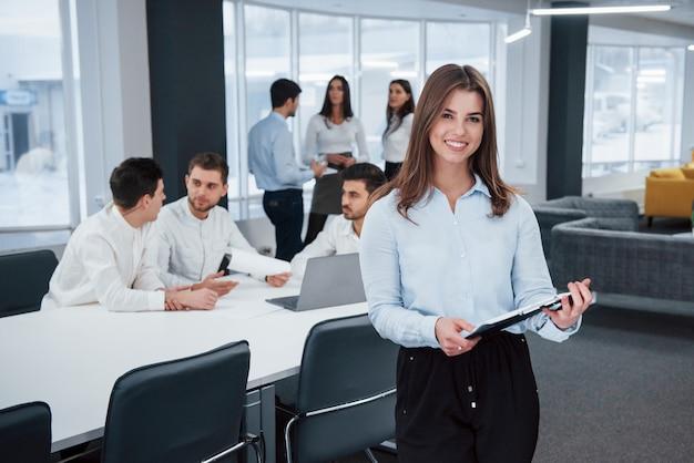 Czuje się dobrze, ponieważ uwielbia swoją pracę. portret młoda dziewczyna stojaki w biurze z pracownikami przy tłem