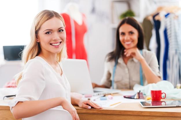Czuję się dobrze z ich nowym projektem. dwie piękne młode kobiety patrzące w kamerę i uśmiechające się siedząc przy stole w warsztacie mody