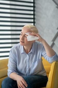 Czuję się niedobrze. dorosła kobieta w bluzce i dżinsach z serwetką przy twarzy, z zamkniętymi oczami, siedząca w fotelu chora.