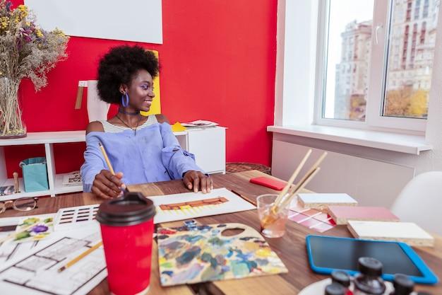 Czuję się niesamowicie. piękny, rozpromieniony projektant czuje się niesamowicie podczas pracy w ładnym, przestronnym biurze