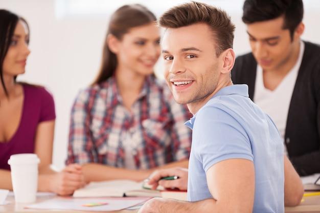 Czuje się pewny swojego egzaminu końcowego. czterech wesołych studentów siedzi razem przy biurku i studiuje, podczas gdy jeden mężczyzna patrzy przez ramię i uśmiecha się