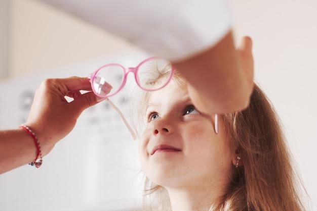 Czuje się podekscytowany. lekarz daje dziecku nowe różowe okulary do jego widzenia.