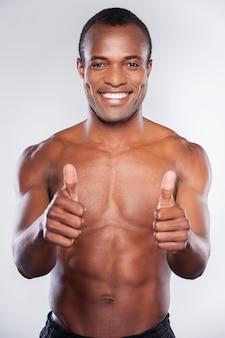 Czuję się silny i zdrowy. młody człowiek z afryki, bez koszuli, uśmiechający się i pokazujący kciuki do góry, stojąc na szarym tle