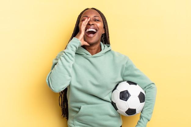Czuję się szczęśliwy, podekscytowany i pozytywnie nastawiony, wydając wielki okrzyk z rękami przy ustach, wołając. koncepcja piłki nożnej
