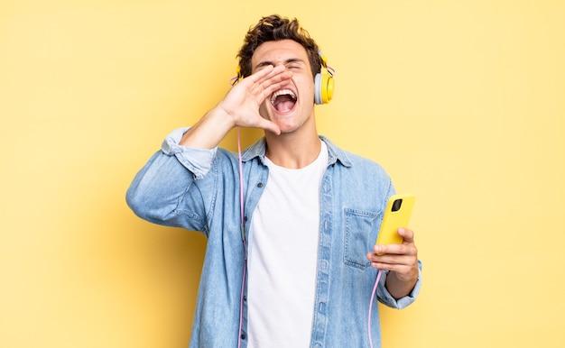 Czuję się szczęśliwy, podekscytowany i pozytywnie nastawiony, wydając wielki okrzyk z rękami przy ustach, wołając. koncepcja słuchawek i smartfona