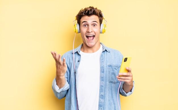 Czuję się szczęśliwy, podekscytowany, zaskoczony lub zszokowany, uśmiechnięty i zdumiony czymś niewiarygodnym. koncepcja słuchawek i smartfona