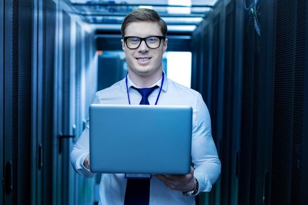 Czuje się szczęśliwy. wesoły młody operator uśmiecha się i trzyma laptopa