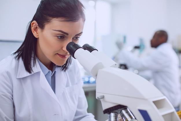 Czuje się szczęśliwy. zadowolona inteligentna naukowiec pracująca z mikroskopem i nosząca mundur