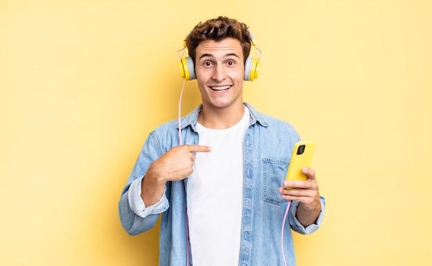 Czuję się szczęśliwy, zaskoczony i dumny, wskazując na siebie z podekscytowanym, zdumionym spojrzeniem. koncepcja słuchawek i smartfona