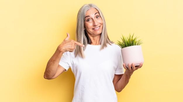 Czuję się szczęśliwy, zaskoczony i dumny, wskazując na siebie z podekscytowanym, zdumionym spojrzeniem trzymający roślinę ozdobną