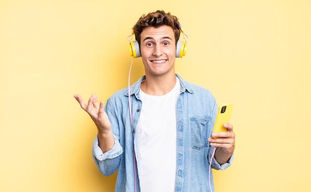 Czuję się szczęśliwy, zaskoczony i pogodny, uśmiechnięty z pozytywnym nastawieniem, realizujący rozwiązanie lub pomysł. koncepcja słuchawek i smartfona