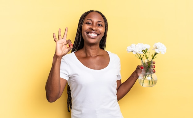 Czuję się szczęśliwy, zrelaksowany i usatysfakcjonowany, okazując aprobatę dobrym gestem, uśmiechając się. koncepcja dekoracyjnych kwiatów